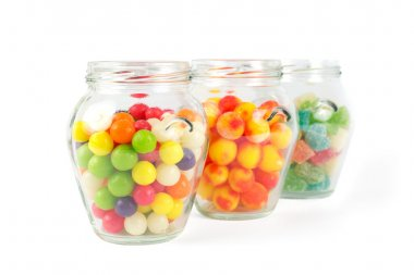 Glass jars filled with different colorful candies isolated on white