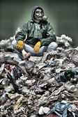 Photo Man in a gas mask sitting on the garbage and holding a bone