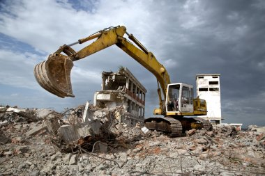 Bulldozer removes the debris from demolition of old derelict buildings at the site stock vector