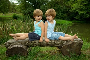 Adorable Little Twin Brothers Sitting on a Wooden Bench, Smiling and Looking at Each Other Near the Lake