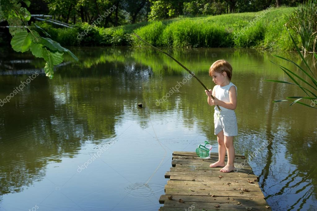 Cute little boy fishing from the edge of wooden dock and for Little boy fishing