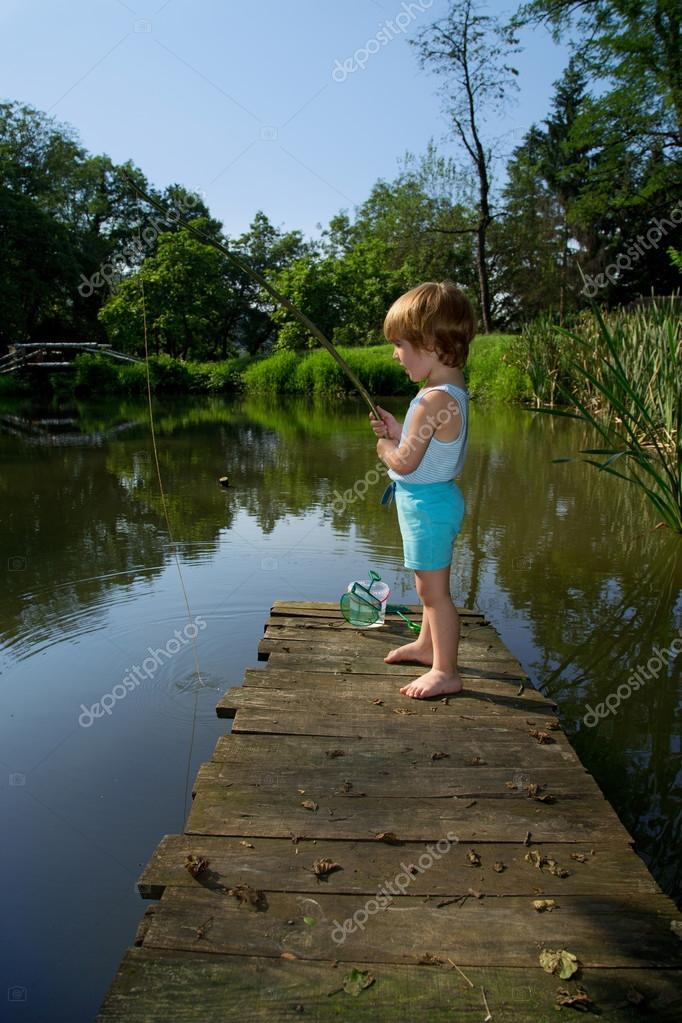 Sweet Little Boy Standing on the Edge of Wooden Dock and Fishing on  Lake in Sunny Day