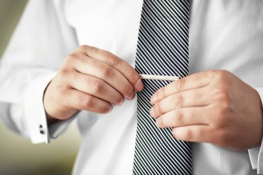 Man putting on tie clip, closeup.