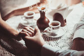 Fotografie paar in Liebe trinken Kaffee im Café, halten einander wird von hand