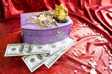 Box for jewelry, dollars and golden Buddha on red background