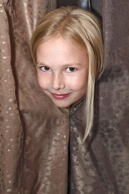 Little girl plays at hide-and-seek looks out because of curtains
