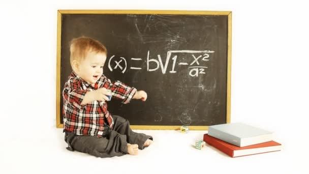 baby boy in front of a blackboard