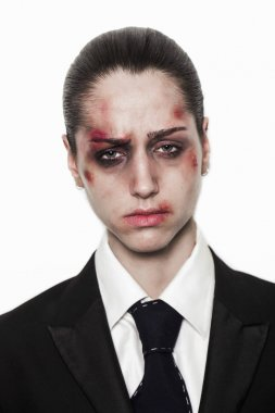 Beaten up girl with sad expression wearing coat and tie