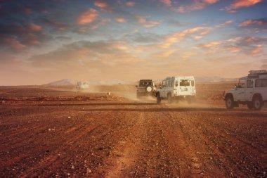 Cars in the desert at sunset