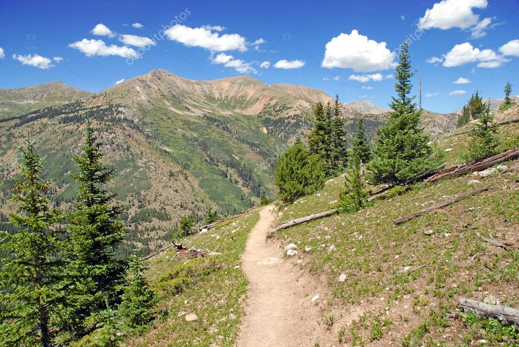 Hiking in the Rocky Mountains with Blue Sky and Clouds