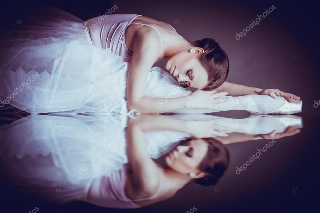 Lying ballerina with the reflection