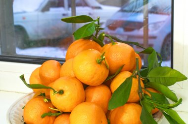 Tangerines with leaves. Winter behind the window.