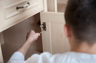 Young man assembling furniture