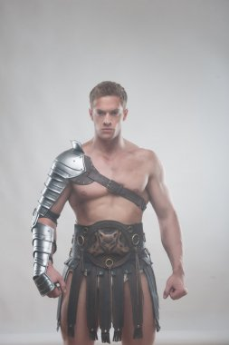 Gladiator in armour posing over grey background