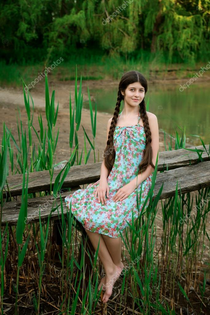 Nice girl sitting in the forest front the lake