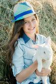 Cute Teen Mädchen mit weißen Kaninchen sitzen vor Heuhaufen