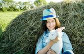 Teen Mädchen mit weißen Kaninchen sitzen vor Heuhaufen