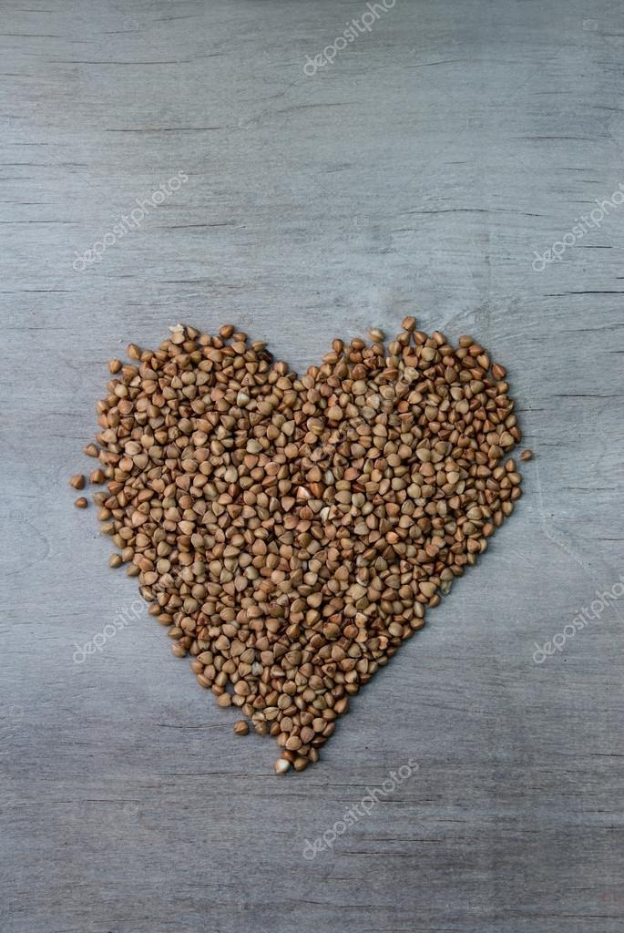 buckwheats grains formed in heart shape on wooden background