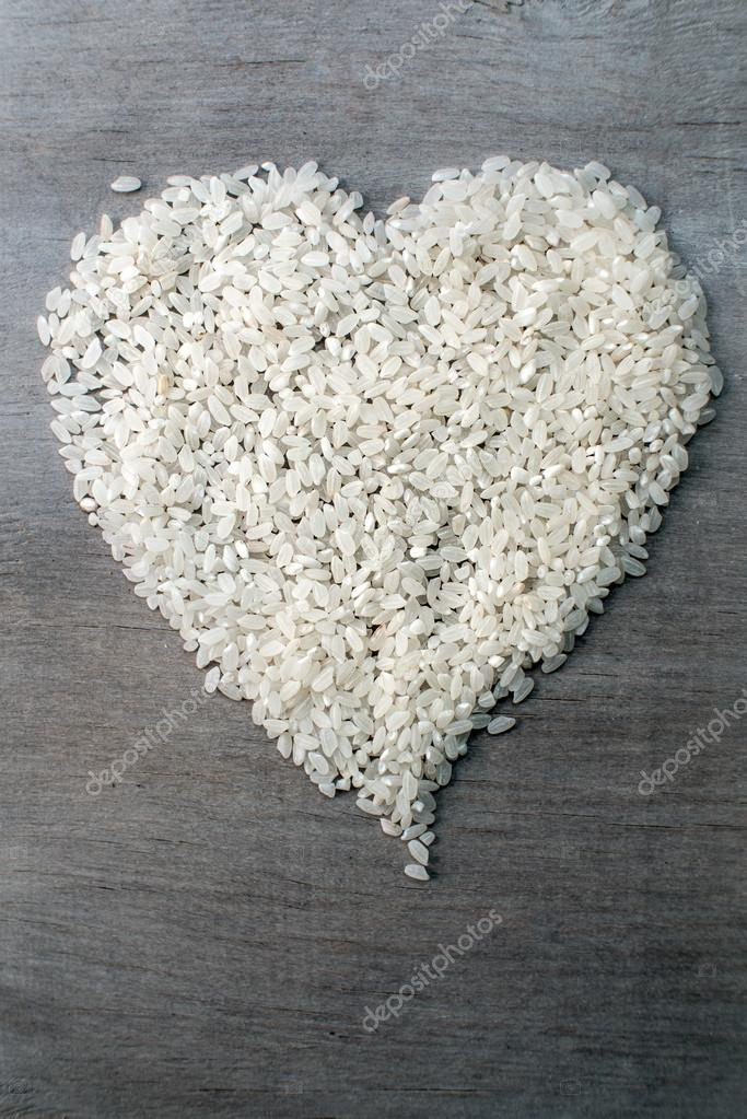 rice grains formed in heart shape on wooden background