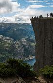 Photo tourists on Preikestolen cliff in Norway, Lysefjord view
