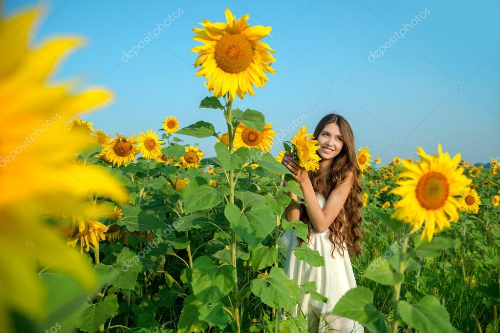 Beautiful young woman with sunflower posing in the sunflowers fi