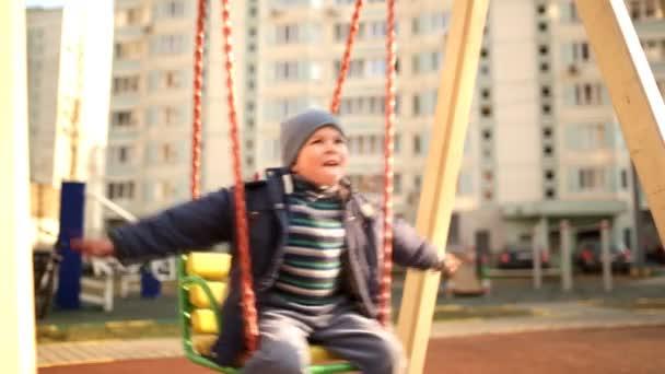 Happy boy swinging on a swing