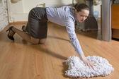 Sekretärin, die den Boden im Büro wäscht
