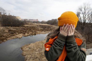 Sad teenager in orange knitten hat and scarf closed her face by hands, stand alone near the scorched field. Spring time