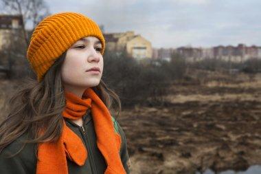 Sad teenager in orange knitten hat