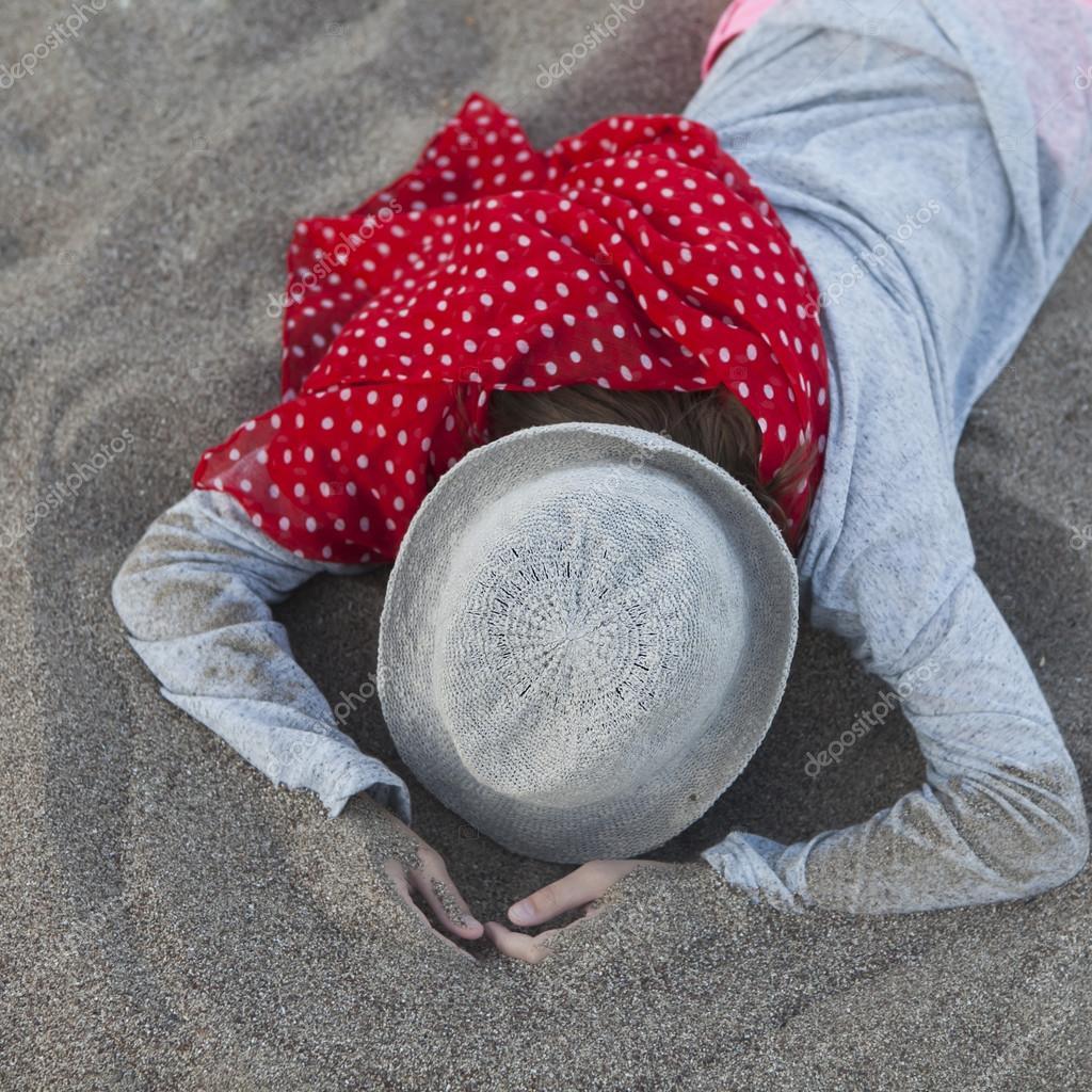 Girl lies on the sand