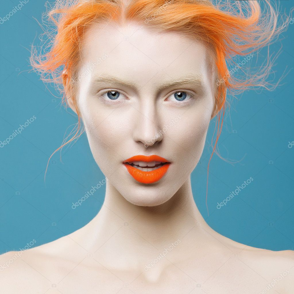 Portrait of beautiful girl with orange hair on a blue background, closeup