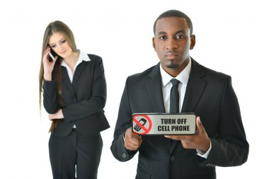 Business man holding Turn off cell phone sign  with serious expression