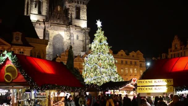 Praha, Česká republika - prosinec 2013: svítící vánoční stromek s vánoční obchody s lidmi - na Staroměstském náměstí. v budově historické pozadí