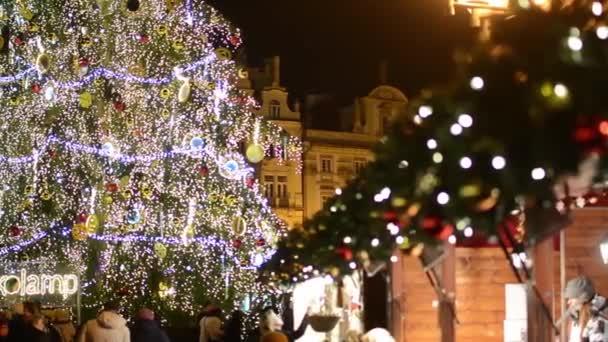Vánoční tržiště (obchody) s lidmi, na náměstí - Svítící dekorace - Staroměstské náměstí - v pozadí historické budově - v noci