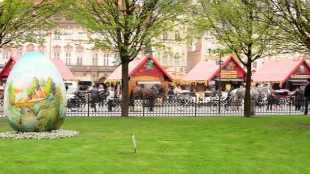 Easter markets - big Easter egg in the park with Easter shops and people. Old Town Square in Prague.