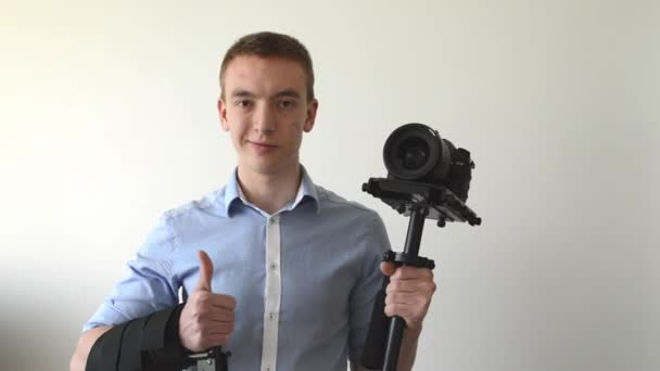 Man with professional camera (steadicam) and smiles