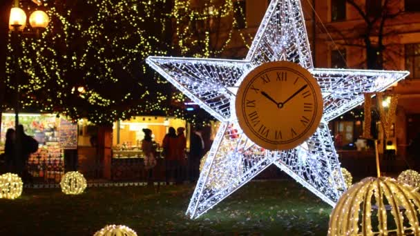 PRAGUE, CZECH REPUBLIC - DECEMBER 2013: Shining Star (with static clock) on the street with people and christmas shops. With shining balls and shining trees (light bulb)