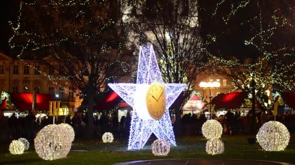 Praha, Česká republika - prosinec 2013: zářící hvězda (s statické hodiny) na ulici s lidmi v pozadí a vánoční obchodech. s zářící koule a