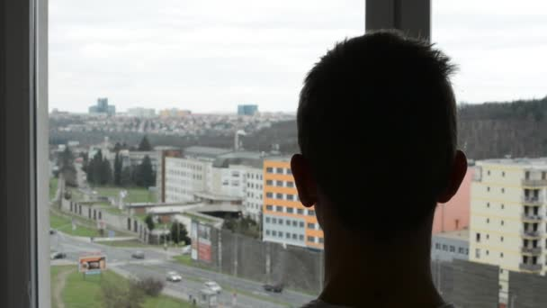 Man looking out the window at the busy street (close up)