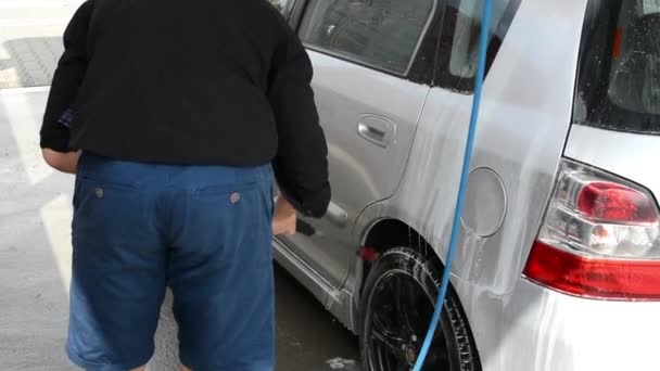Man washing car with water (spray hose)