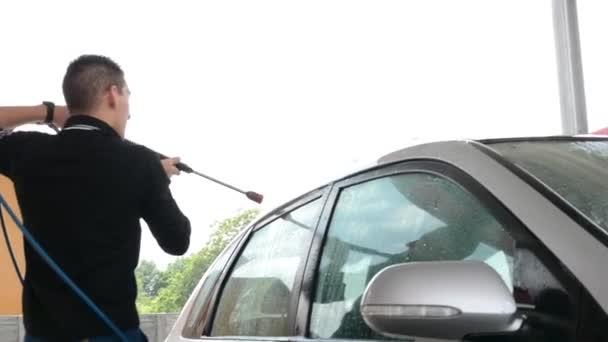 Man washing car with water (spray hose)
