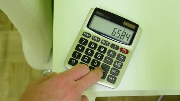 Kalkulačka na stůl - muž se počítá na kalkulačce