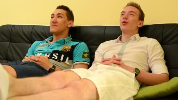 due amici seduti su un divano e parlare e guardare la tv