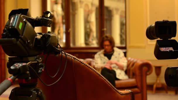 Interview with woman - television cameras (studio) - historic interior in background