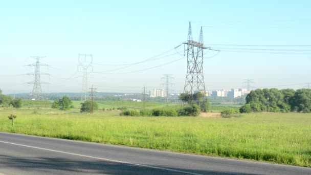 High voltage to the road with nature. City in the background