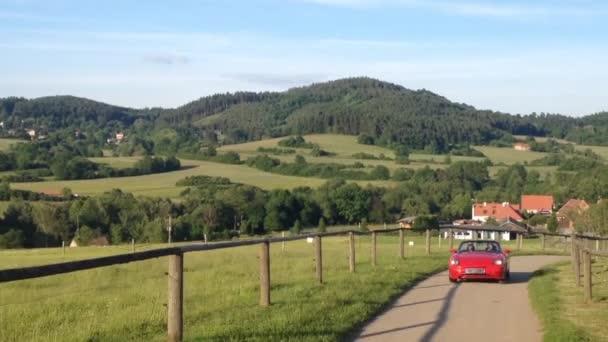 muž a žena cestovat v kabrioletem na silnici - příroda v pozadí