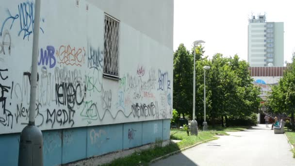 Graffiti on the wall of a block of flats with the street (park with building)