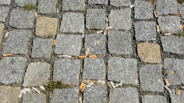 nedopalky cigaret na kamenné dlažbě