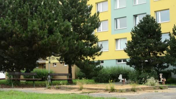 staré dětské hřiště a příroda s byty v pozadí