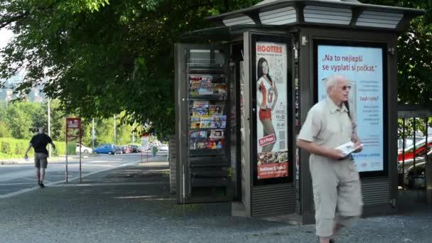 pouličních stáncích - muž s noviny a žena - městské ulice s auty